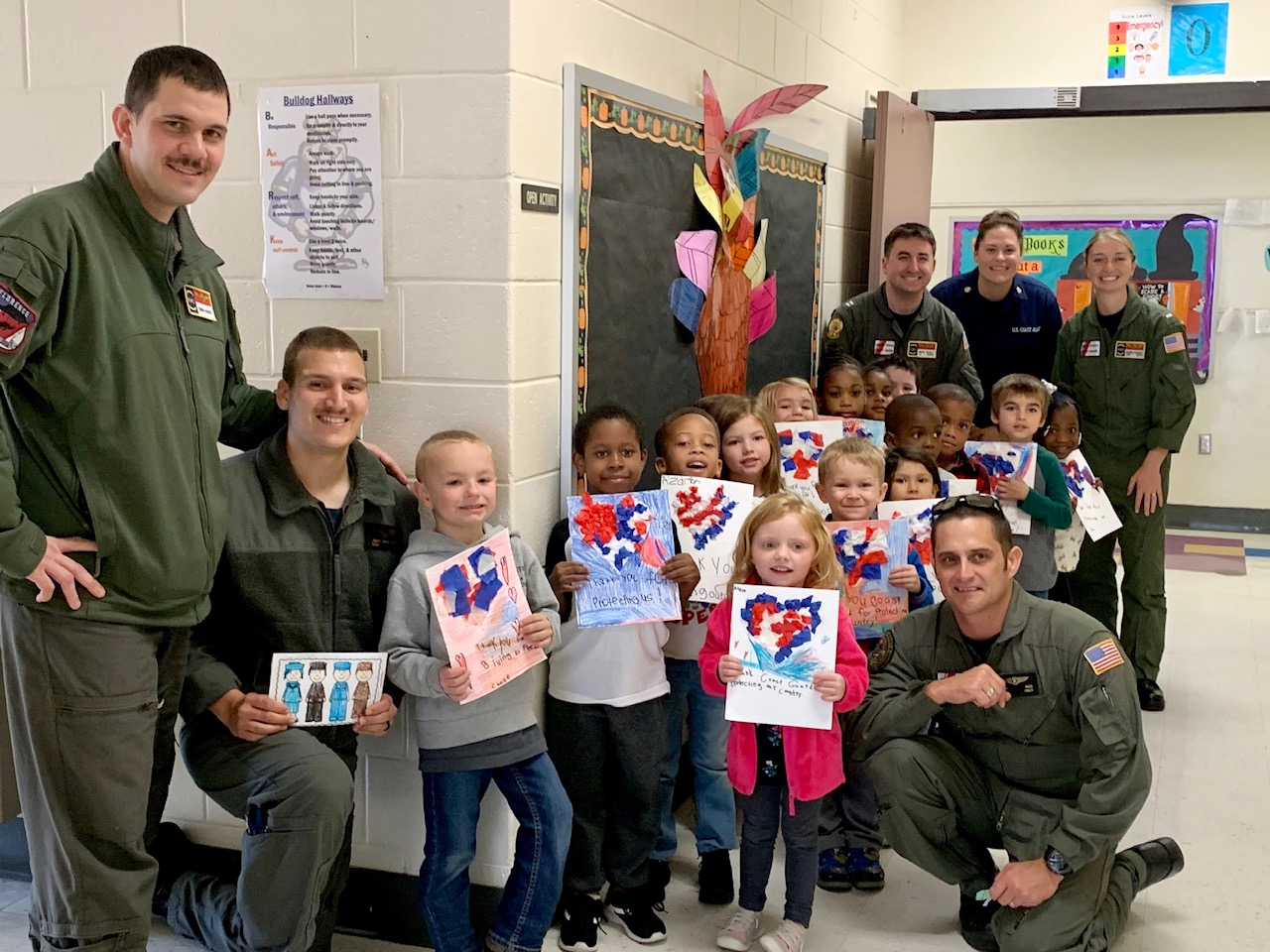 volunteer Coast Guard members with local students showing artwork at school